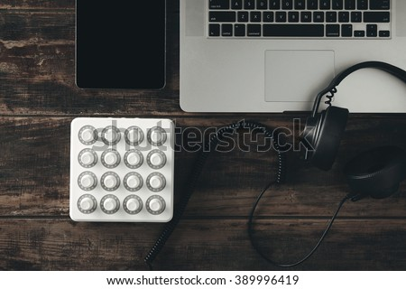 Top view portable travel on way music production set: midi mixer control. smartphone tablet, retina laptop, black dj headphones with leather earpad and long twisted cort on aged table - stock photo