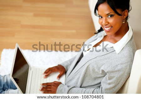 Top view portrait of a beautiful girl smiling and looking to you while sitting on floor in front her laptop at home indoor - stock photo