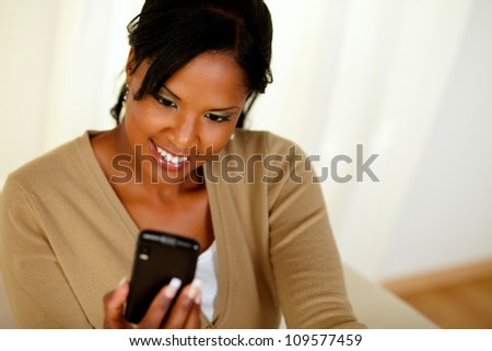 Top view portrait of a charming black lady sending a message by cellphone - stock photo