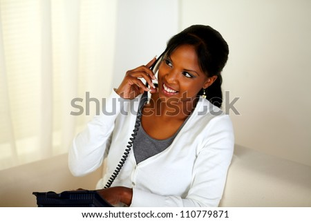 Top view portrait of a pretty woman conversing on phone while sitting on sofa at home indoor