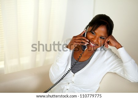 Top view portrait of a relaxed black girl smiling and conversing on phone while sitting on couch at home indoor