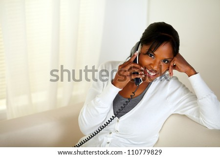 Top view portrait of a smiling black woman looking at you while talking on phone