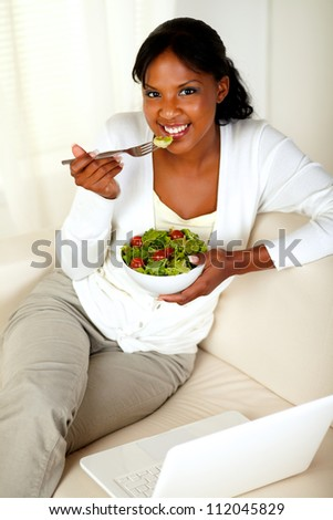 Top view portrait of a young female eating healthy salad and looking at you while is sitting on couch in front of her laptop - stock photo