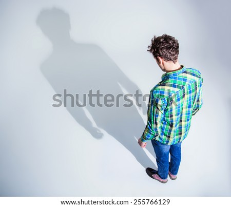 Top view portrait of a young man in colourful wear standing over gray backgorund - stock photo