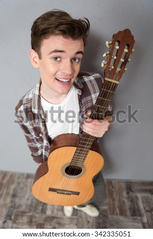 Top view portrait of a young man standing with guitar and looking at camera - stock photo