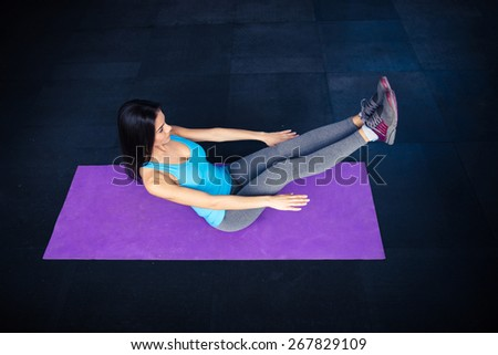 Top view portrait of a young woman doing excercise on yoga mat at gym - stock photo