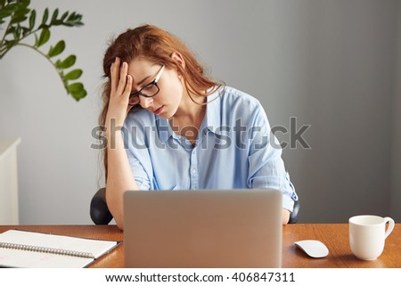 Top view portrait of dissatisfied young female office worker looking unhappily at the camera, leaning on her elbow while sitting at wooden table in front of computer screen during hard working day   - stock photo
