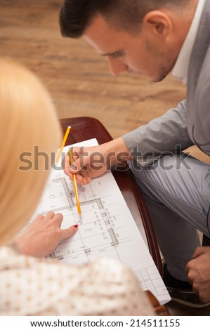 Top view portrait of young handsome architect discussing ground plan with client sitting at the table in design studio, pointing at architectural plan with pencil - stock photo