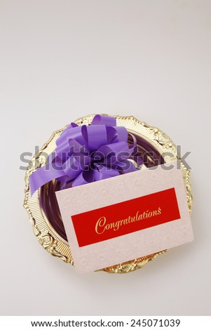 top view purple ribbon bow and a congraturation card - stock photo