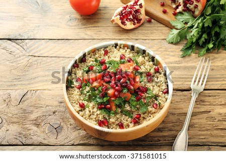 top view quinoa salad with pomegranate on rustic kitchen table - stock photo
