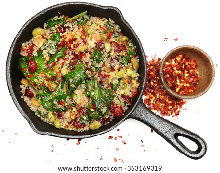 Top View Quinoa Spinach and Cranberry Salad in Cast Iron Skillet with crushed red pepper.