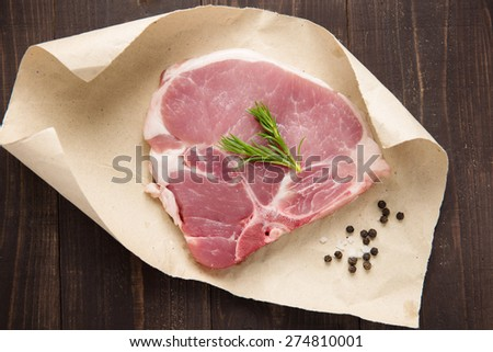 Top view raw pork chop steak on paper and wooden background. - stock photo