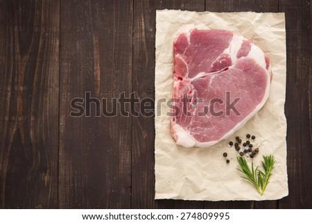 Top view raw pork chop steak on wooden background. - stock photo