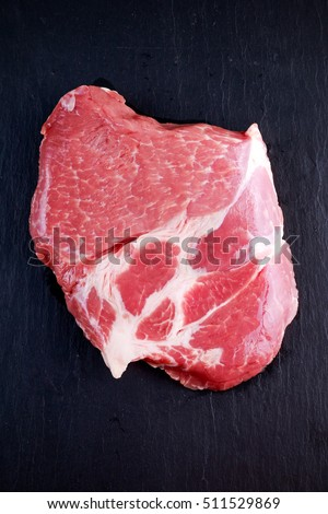 Top view raw pork rib eye steak on stone background
