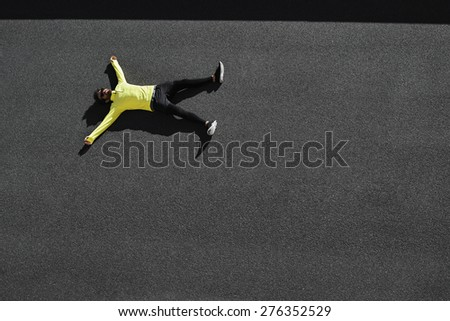 Top view runner in yellow sportswear resting lying on a black asphalt after running. Jogging man taking a break during training outdoors. Caucasian fitness model 20s in Barcelona, Spain.  - stock photo