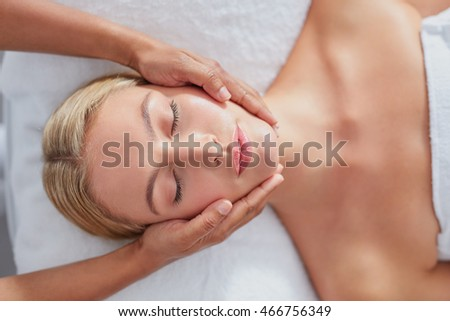 Top view shot of a beautiful young woman getting a facial massage at a spa