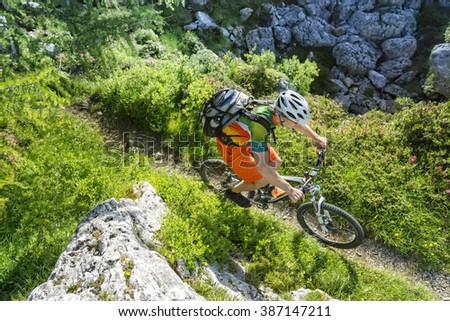 Top view shot of a mountain biker riding a single trail in the mountains - stock photo