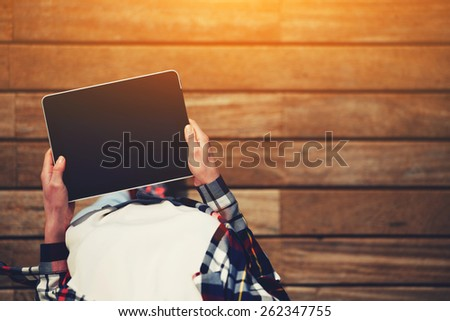 Top view shot of a woman holding digital tablet with a blank screen- closeup, fem a hands holding blank digital tablet against beautiful wooden copy space area, flare sun light, filtered image - stock photo