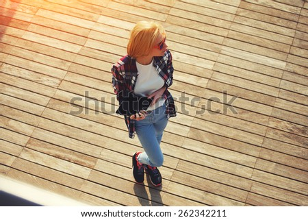 Top view shot of a young student girl standing with her digital tablet outdoors at sunny day, caucasian college student holding tablet while standing at campus looking away, flare sun light - stock photo