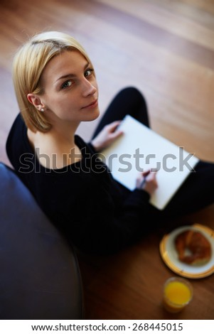 Top view shot of blonde hair young woman drawing on the paper while sitting on the floor of her living room, creative artist teenager girl having breakfast while painting on sheet of album paper - stock photo