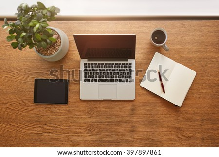 Top view shot of laptop computer, digital tablet, potted plant, diary and a cup of coffee on wooden table. Modern work desk with copy space. - stock photo