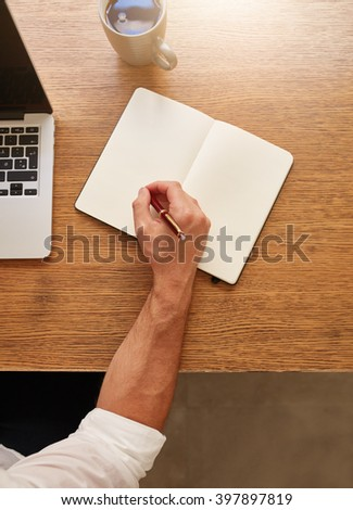 Top view shot of man making some notes in his diary while sitting at his working place. - stock photo