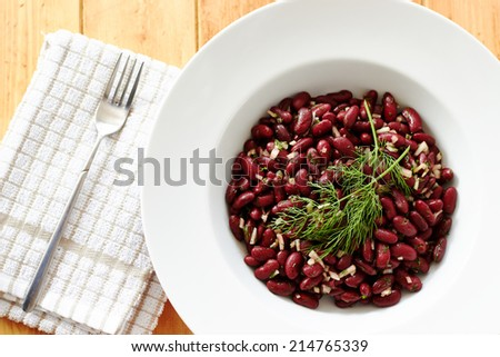 Top view showing cooked kidney beans on a white plate and wooden table  - stock photo