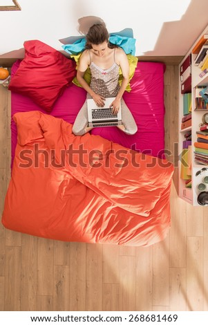 top view, single young woman using a laptop in bed by a sunny morning, the bedding has bright colors