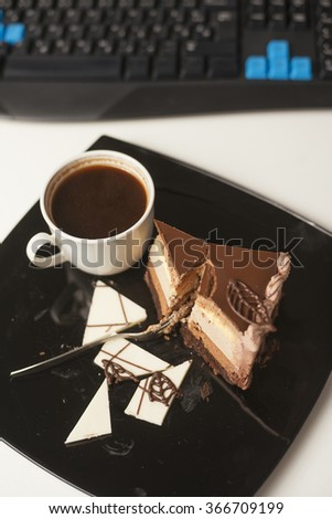 Top view slice of cake on plate, cup of coffee and keyboards on table - stock photo