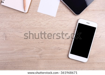 Top view smartphone, tablet and office supplies on wooden background