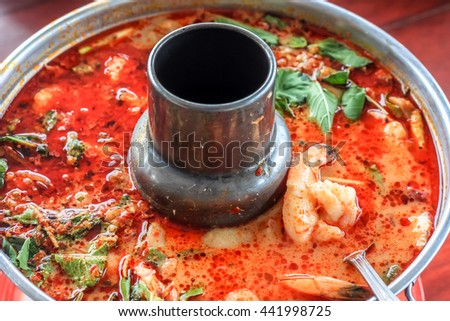 Top view spicy tom yum goong Thai style in the hot pot, spicy soup, a classic spicy lemongrass and shrimp soup recipe from Thailand - stock photo