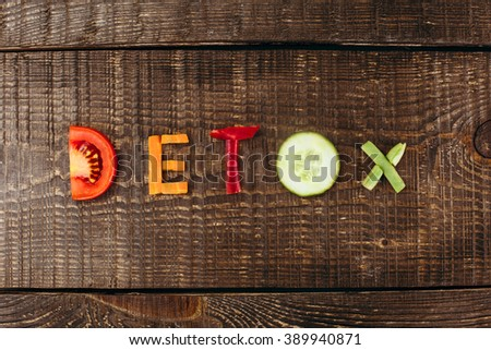 "Top view studio shot of fresh vegetables on wooden table. There are vegetables in shape of word ""detox"" - stock photo"