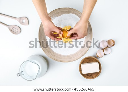 Top view studio shot of ingredients for homemade baking. Making dough by female hands - stock photo