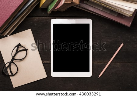 top view tablet pc with old book on reading table - stock photo