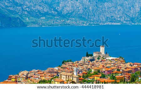 Top view to ancient tower and fortress in old town malcesine at garda lake veneto region italy mountains on background summer landscape with colorful houses roofs green trees - stock photo