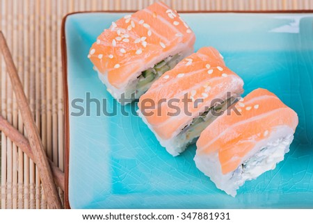 Top view to california maki sushi with fish and chopsticks. Roll made of salmon, cream cheese and  cucumber.  - stock photo