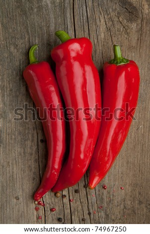 Top view to red paprika on wooden background