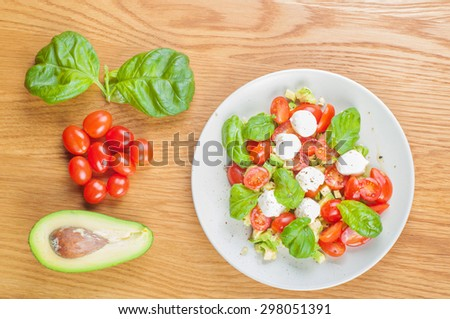Top view to the salad with avocado, tomatoes and basil on the wooden table - stock photo