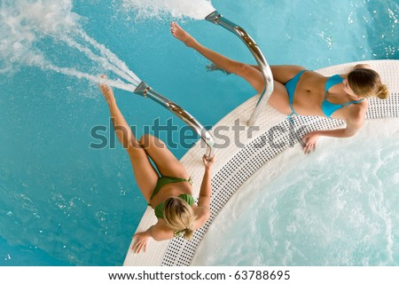 Top view - two woman relax in swimming pool sitting at bubble bath - stock photo