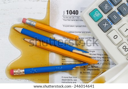 Top view U.S. Individual tax form 1040, coffee spilled out of paper cup,  with partial old calculator and broken pencils on wooden desktop. - stock photo