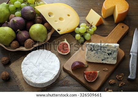 top view Various types of cheese and fruit on rustic wooden table - stock photo