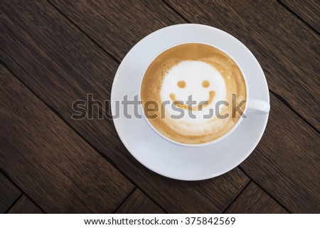 Top view white cup of latte art happy smile face on brown wooden table background with copyspace. - stock photo