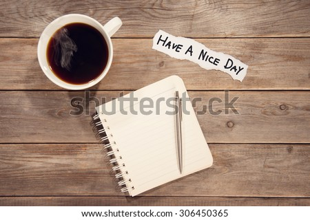 Top view work space with booklet, pen, cup of coffee and note message Have A Nice Day. Wooden table background in vintage toned. - stock photo