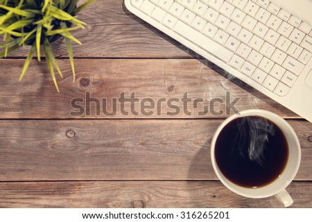 Top view work space with computer keyboard, cup of coffee and plant pot. Wooden table background soft focus with noise in vintage toned. - stock photo