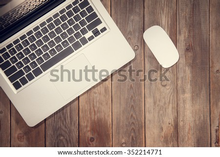 Top view working desk with laptop computer. Wooden table background with copy space in vintage toned. - stock photo