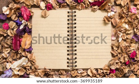 Top view workspace with blank notebook and dried flowers on wooden table background . - stock photo