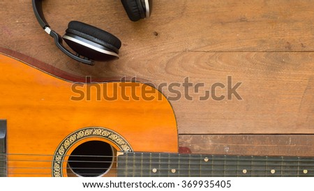 Top view workspace with headphone and acoustic guitar on wooden table background .Free space for your text. - stock photo
