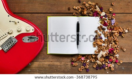 Top view workspace with notebook,pen,electric guitar  and dried flowers on wooden table background . - stock photo