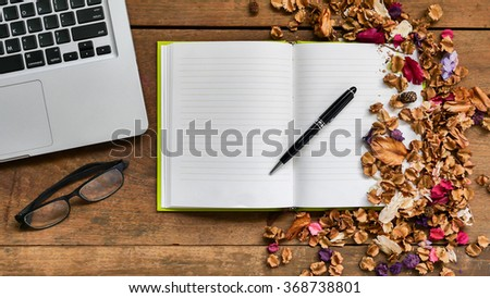 Top view workspace with notebook,pen,glasses,laptop and dried flowers on wooden table background . - stock photo