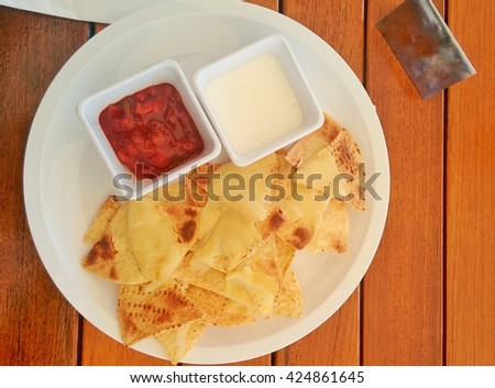 Top view yellow nacho cheese and sauce on wooden table - stock photo
